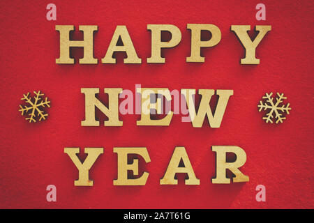 Happy New Year background.Hand made home decor.Rustic wooden letters on vibrant red backdrop.Winter holiday wallpaper edited with vintage film filter - Stock Photo