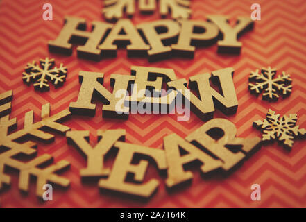 Happy New Year background.Red stripped backdrop and rustic wooden letters edited with old film filter.Winter holiday wallpaper in vintage style - Stock Photo