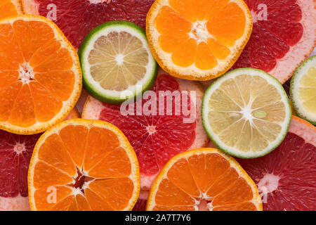 Background flat lay halves of citrus, orange, lime and grapefruit. View from above. - Stock Photo