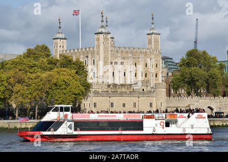 One of the City Cruises' London sightseeing boats on the river Thames passing the Tower of London - Stock Photo