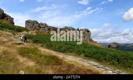 People walking on path to high sunlit rocky outcrop under blue sky - scenic landscape of Cow and Calf Rocks, Ilkley Moor, West Yorkshire, England, UK. - Stock Photo