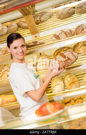 Angestellte in der Bäckerei, Junge Frau verkauft Backwaren, Brotregal, Brot, - Stock Photo