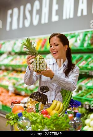 Frau geht Einkaufen im Supermarkt, kauft eine Ananas, Einkaufswagen mit Obst, Gemüse und Lebensmittel,  MR: Yes - Stock Photo