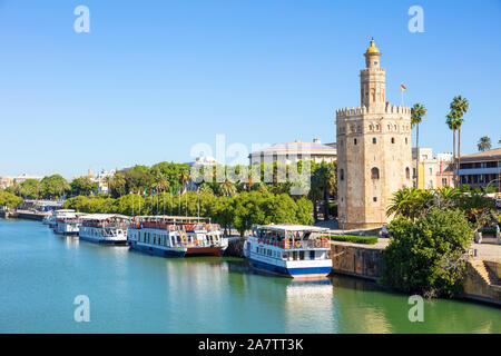 Tour boats moored on the Guadalquivir river bank near the Torre del Oro Seville Spain Paseo de Cristóbal Colón seville Andalusia EU Europe - Stock Photo