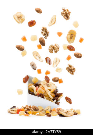 Dried fruits jumping out white bowl on white background - Stock Photo