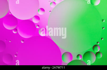 Colorful abstract background. Pink, green circles and oil bubbles in the water closeup. Macro abstraction. Rainbow oil texture and pattern. - Stock Photo