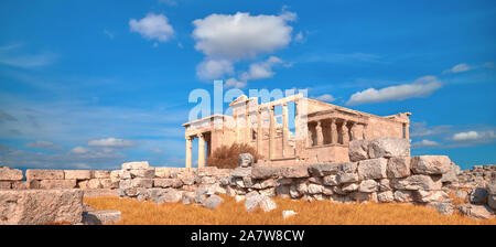 Panoramic image of Erechtheion temple Acropolis, Athens, Greece, with famous Caryatides in Autumn with orange grass and beautiful blue sky with feathe - Stock Photo