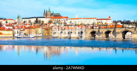 Charles Bridge, St. Vitus Cathedral and other historical buildings in Prague, panoramic image from the riverside with reflection in Vltava river, roma - Stock Photo