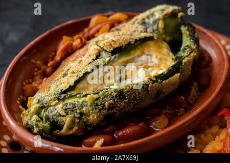 Chilles rellenos and Mexican rice served in traditional clay plates - Stock Photo