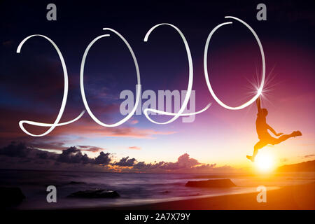 young man jumping on the beach. happy new year 2020 concepts - Stock Photo