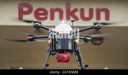 Penkun, Germany. 04th Nov, 2019. A drone transports a defibrillator to the sky of Penkun. Defibrillators are small devices that can 'turn on' the heart again with an electric shock in the event of cardiac arrest. A project team at Greifswald University Hospital is planning to fly defibrillators with drones to patients and medically trained first responders. The aim is to develop a system that deploys drones in such a way that they close the gaps in primary care in the countryside. In the district of Vorpommern-Greifswald a feasibility study is now starting. Credit: Stefa/dpa/Alamy Live News - Stock Photo