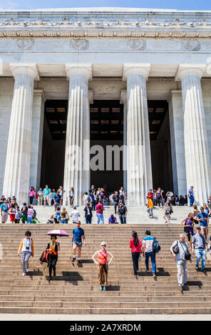 A woman stand for a portrait low on the steps up to the Lincoln Memorial with lots of other people around her, Washington DC, USA. - Stock Photo