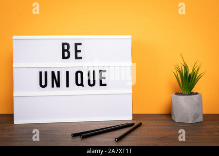 Be unique Concept for being different, successful, persistent and progressive. White lightbox on a wooden table