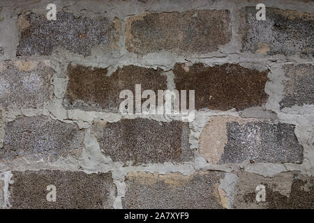 Gray block wall background. Grey textured building exterior surface with rough stacked big bricks. Tiled structure of stonewall for backdrop designs - Stock Photo
