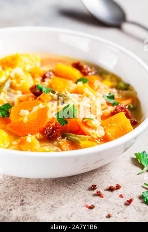 Vegetarian vegetable soup with lentils and pumpkin in a white plate. Healthy vegan food concept. - Stock Photo