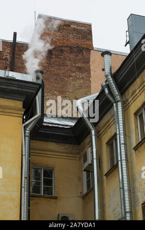 Walls of old houses with silvery pipes ventilation system with smoke over one of the pipes vertical orientation - Stock Photo