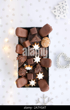 German gingerbread assortment in cookie tin with Christmas decoration and fairy lights. Top view. - Stock Photo