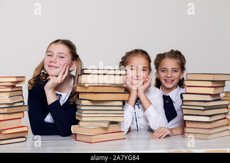three schoolgirl girls with books in the library in class at the desk - Stock Photo