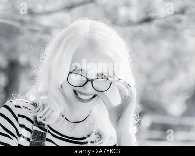 Backlighted portrait headhot eyeshot beautiful mid-adult woman in nature very happy smiling at camera peeking over spectacles - Stock Photo