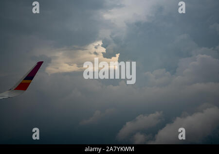 Wing of plane over the city. Airplane flying on blue sky. Scenic view from airplane window. Commercial airline flight in the morning with sunlight. - Stock Photo