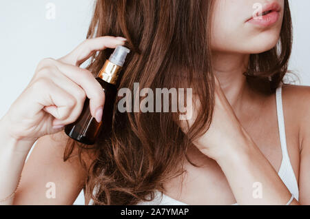 a woman with beautiful hair holds hair oil. The concept of hair care - Stock Photo