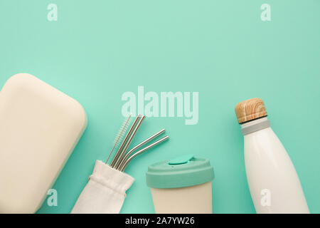 Reusable stylish bamboo lunch box, coffee cup, metal straws and water bottle on light blue background. Flat lay, top view. Copy space. Zero waste, red - Stock Photo