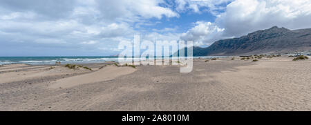 panoramic shot of Playa de Famara beach and mountain range on Lanzarote , Canary Islands, against ocean and sky - Stock Photo
