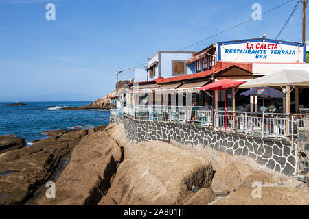 Restaurant, Terrace Bar, Cafe on the seafront in the early morning at La Caleta, Costa Adeje, Tenerife, Canary Islands, Spain - Stock Photo