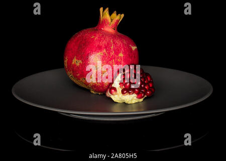 Group of one whole one piece of fresh red pomegranate on gray ceramic plate isolated on black glass - Stock Photo