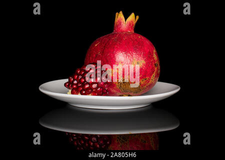 Group of one whole one piece of fresh red pomegranate on white ceramic plate isolated on black glass - Stock Photo