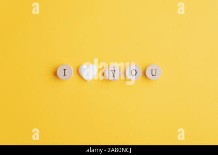 I love you sign spelled on wooden cut circles with a marble heart shape in between. Over yellow background with copy space. - Stock Photo