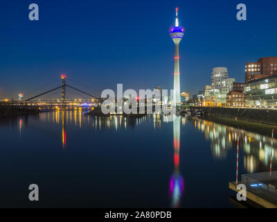 Dusseldorf by night from the Hafen, with Rheinturm, Neuer Zollhof buildings from Frank Gehry and the Fussgängerbrücke. Business center in Europe. - Stock Photo