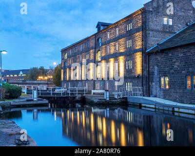 Floodlit Canal Warehouse reflected in the Leeds and Liverpool Canal at dusk Granary Wharf Leeds West Yorkshire England Stock Photo