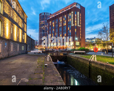 Old canal warehouse by the River Lock and modern hotel at Granary Wharf at dusk Leeds West Yorkshire England Stock Photo