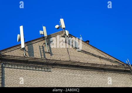 Antennas, mount and cables cellular communication are located on the building gable against the blue sky - Stock Photo