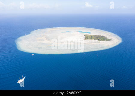 A Pinisi schooner drifts near the remote, tropical island of Midorang in the Ceram Sea. This area harbors extremely high marine biodiversity. - Stock Photo