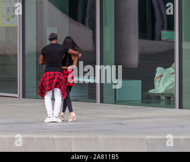 Young multi-ethnic couple of salsa dancers performs in the street - Stock Photo
