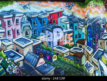 Part of a street art mural by artist Silent Hobo at Montpelier railway station in Bristol showing colourful houses spelling out the location - Stock Photo