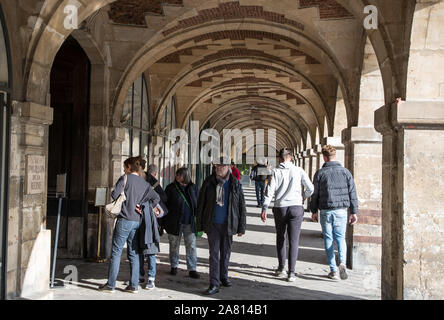 Paris, France - 3rd October 2019: Tourisrs walking through the outdoors arched hallways of buildingg around Place des Vosge - Stock Photo