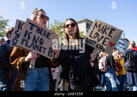 two young women protesting against current politics regarding the worldwide climate change crisis with protest signs in their hands - Stock Photo