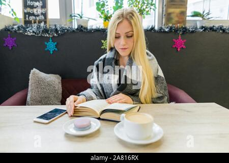 Young beautiful blonde girl sitting in coffee shop reading book. Winter season - Stock Photo