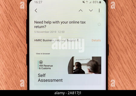 An email on a smartphone from the UK HM Revenue and Customs asking for a self assessment tax return to be submitted for the 2018 - 2019 tax year - Stock Photo