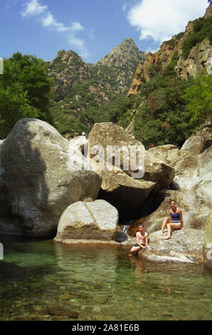 Gorges d'Héric, Monts de l'Espinouse, Hérault, Occitanie, France: two children cool off in a rock pool during a Summer hike.  MODEL RELEASED - Stock Photo