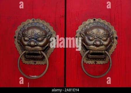 Beijing, China - July 8, 2013: detail from red door, two dragon figures as door handle - Stock Photo