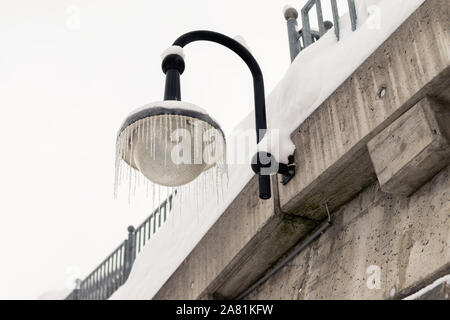 Outdoor street lantern hanged on concrete wall covered with icicles on cold winter day. Winter weather season background - Stock Photo