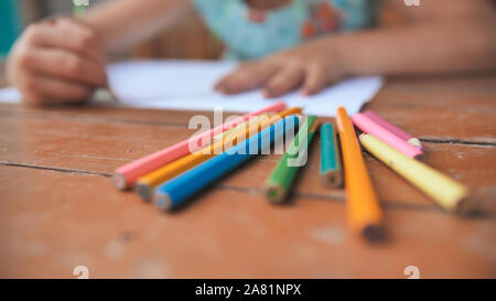 Little six-year-old girl draws with colored pencils. Close-up view of pencils. - Stock Photo