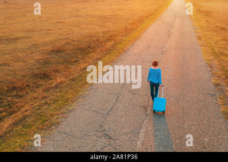 Woman pulling travel suitcase luggage on road in autumn sunset, high angle view from drone pov - Stock Photo