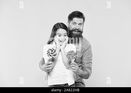 Lovely surprise. Girl cheerful child and dad hold colorful lollipops. Sweet dessert concept. Bearded hipster good daddy for adorable daughter. Daughter and father eat sweet candies. Sweet childhood. - Stock Photo
