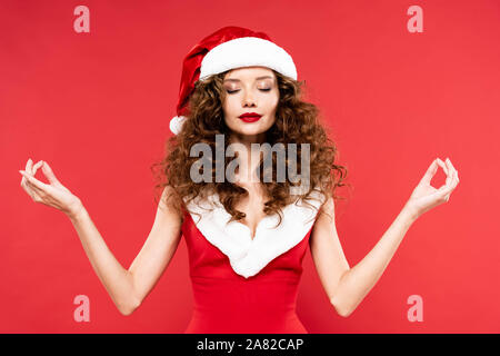 calm curly girl posing in santa costume with gyan mudra signs, isolated on red - Stock Photo