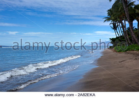 Paradise found on the island of Maui secluded sandy beaches tropical foliage splashing waves hitting the shore - Stock Photo